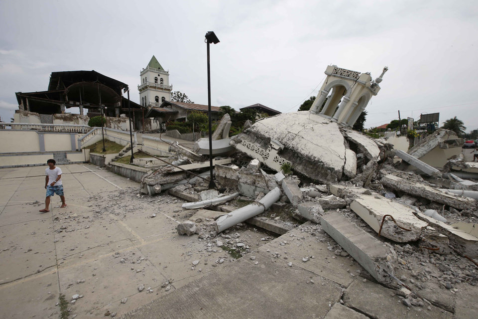 Photo - A boy walks away from the rubble of San Isidro de Labrador church which was caused by a 7.2-magnitude earthquake  at Tubigon township, Bohol province in central Philippines Wednesday Oct. 16, 2013. A 7.2-magnitude quake hit Bohol and Cebu provinces Tuesday damaging churches, buildings and homes and causing multiple deaths across the central region. (AP Photo/Bullit Marquez)