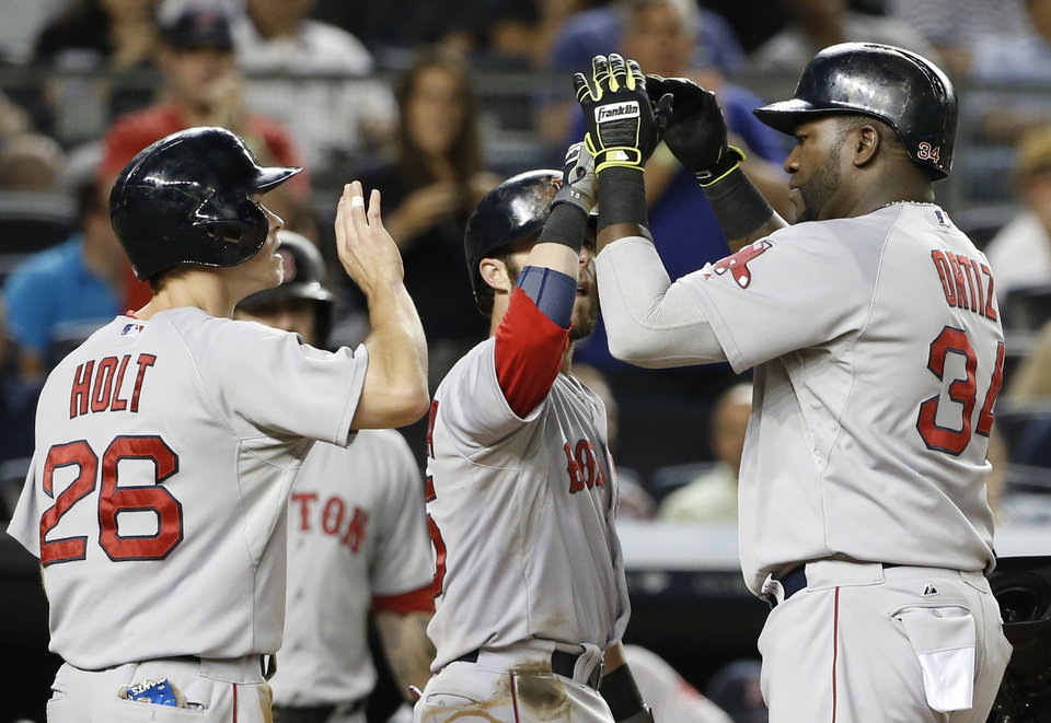 Photo - Boston Red Sox's Brock Holt (28) and Dustin Pedroia, center, greet Red Sox designated hitter David Ortiz (34) at the plate after scoring on Ortiz's third-inning, three-run, home run in a baseball game at Yankee Stadium in New York, Sunday, June 29, 2014.  (AP Photo/Kathy Willens)