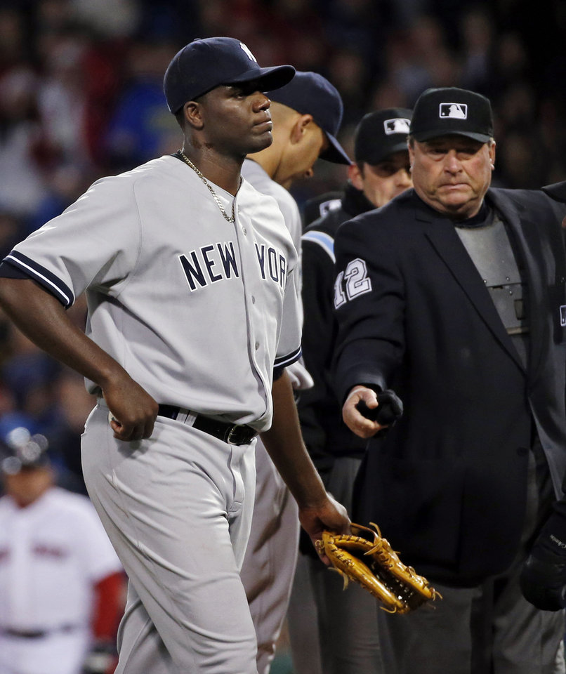 Photo - Home plate umpire Gerry Davis ejects New York Yankees starting pitcher Michael Pineda after a foreign substance was discovered on his neck in the second inning of the Yankees' baseball game against the Boston Red Sox at Fenway Park in Boston, Wednesday, April 23, 2014. (AP Photo/Elise Amendola)