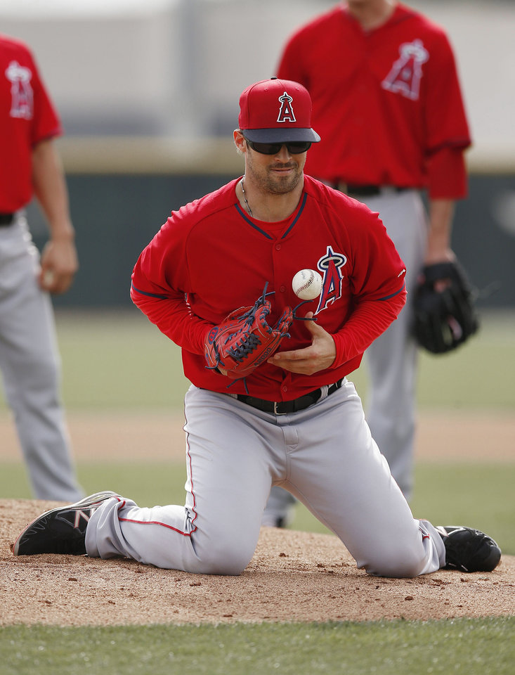 Photo - Los Angeles Angels' C.J. Wilson squats on the ground as he stops a ground ball during pitcher fielding drills during spring training baseball practice on Tuesday, Feb. 25, 2014, in Tempe, Ariz. (AP Photo/Ross D. Franklin)