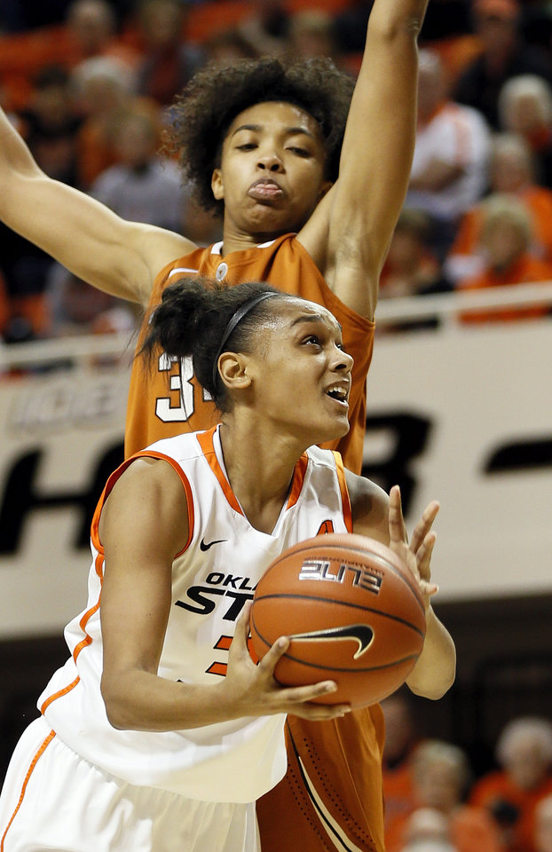 Photo - Oklahoma State's Kendra Suttles (31) takes the ball to the basket against Texas' Imani McGee-Stafford (34) during a women's college basketball game between Oklahoma State University (OSU) and the University of Texas at Gallagher-Iba Arena in Stillwater, Okla., Saturday, March 2, 2013. OSU won, 64-58. Photo by Nate Billings, The Oklahoman