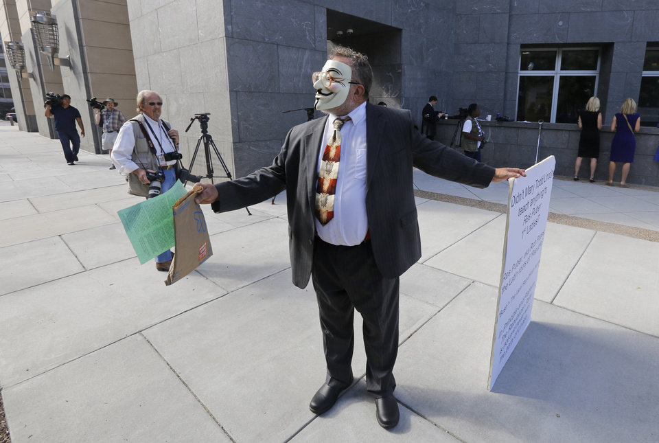 Photo - A masked demonstrator hands out literature in front of federal court where the trial of former Virginia Gov. Bob McDonnell  is being held Wednesday, Aug. 20, 2014,  in Richmond, Va. The demonstrator who declined to give out his name, protested the greed of the former governor and his wife. The  defense continues to present its case in the McDonnell's corruption case.  (AP Photo/Steve Helber)