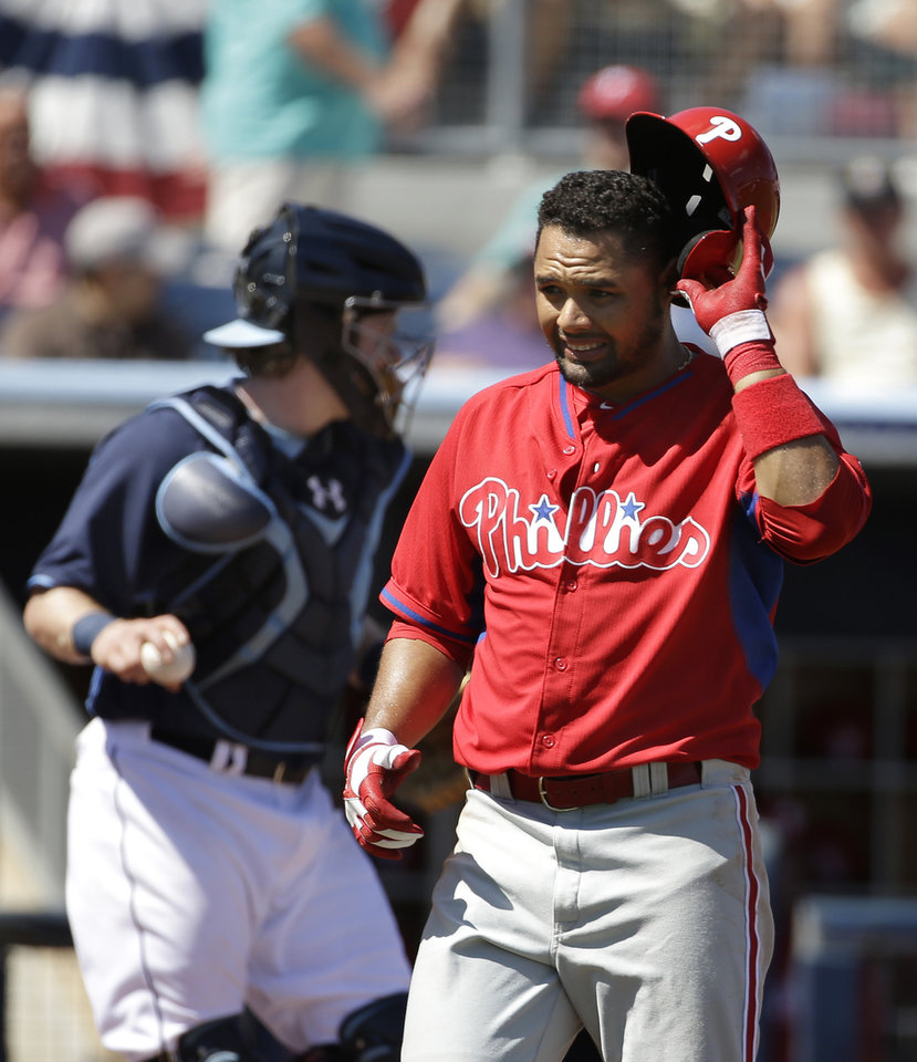 Photo - Philadelphia Phillies' Andres Blanco steps away from the batters box after  the bat slipped out of his hands on a swing as Tampa Bay Rays catcher Ryan Hanigan, left, looks on in the first inning an exhibition baseball game, Monday, March 3, 2014, in Port Charlotte, Fla. (AP Photo/Steven Senne)