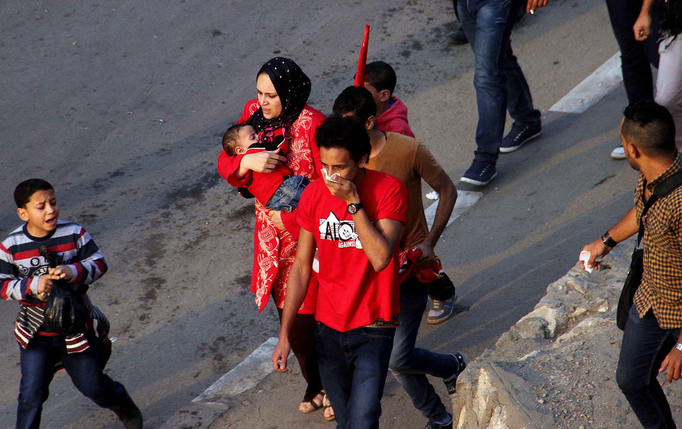 Photo - A mother rushes with her child during clashes between police and supporters of Egyptian club Al Ahly outside a stadium ahead of the African Champions League final in Cairo, Egypt, Sunday, Nov. 10, 2013. Police used tear gas Sunday to disperse the crowd as they threw rocks and tried to push their way into the stadium, many with no tickets. (AP Photo/Mostafa Darwish)