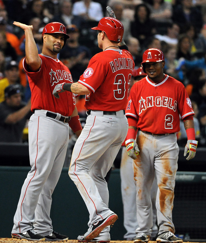 Photo - Los Angeles Angels' Josh Hamilton, center, celebrates his three-run home run with teammate Albert Pujols, left, as Erick Aybar (2) looks on in the sixth inning of a baseball game against the Houston Astros, Friday, April 4, 2014, at Minute Maid Park in Houston. (AP Photo/Eric Christian Smith)