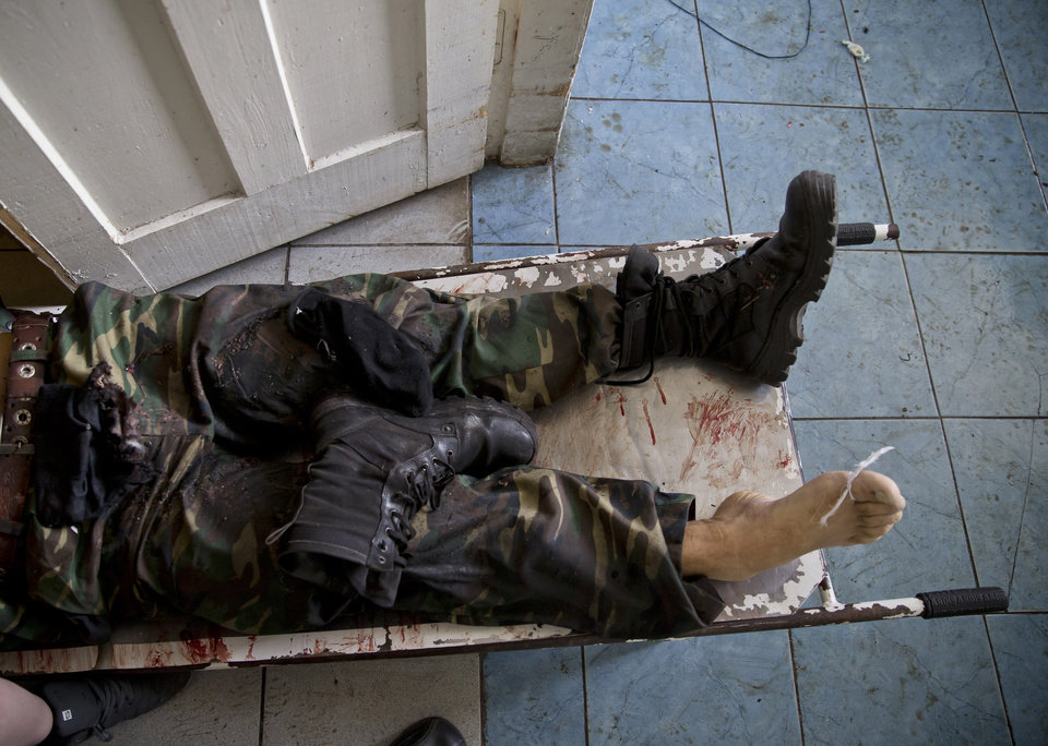 Photo - The body of a pro-Russian gunam killed in clashes with Ukrainian government forces around the airport lies on a stretcher at a city morgue in Donetsk, Ukraine, Tuesday, May 27, 2014. The eastern city of Donetsk was in turmoil Tuesday a day after government forces used fighter jets to stop pro-Russia separatists from taking over the airport. Dozens were reported killed and the mayor went on television to urge residents to stay indoors. (AP Photo/Vadim Ghirda)