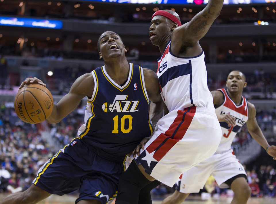 Photo - Washington Wizards  forward Al Harrington stops a drive by Utah Jazz point guard Alec Burks (10) during the second half of an NBA basketball game on Wednesday, March 5, 2014, in Washington. The Wizards defeated the Jazz 104-91. At right is Washington Wizards shooting guard Bradley Beal. (AP Photo/ Evan Vucci)