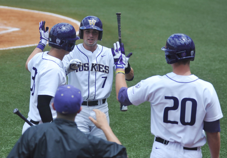 Photo - Washington's Braden Bishop (7) is congratulated by teammates Branden Berry (36) and Trevor Mitsui (20) after scoring against Georgia Tech at the NCAA Oxford Regional at Oxford-University Stadium on Saturday, May 31, 2014. (AP Photo/Oxford Eagle, Bruce Newman)