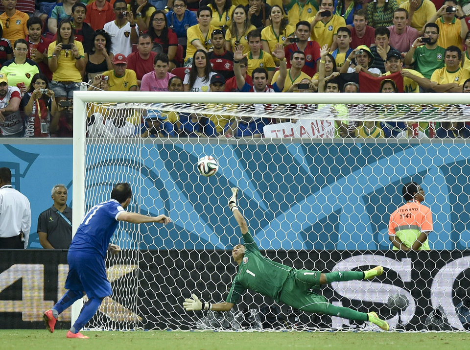 Photo - Costa Rica's goalkeeper Keylor Navas makes a save on Greece's Fanis Gekas penalty shot during a shootout after regulation time in the World Cup round of 16 soccer match between Costa Rica and Greece at the Arena Pernambuco in Recife, Brazil, Sunday, June 29, 2014. Costa Rica defeated Greece 5-3 in penalty shootouts after a 1-1 tie. (AP Photo/Martin Meissner)