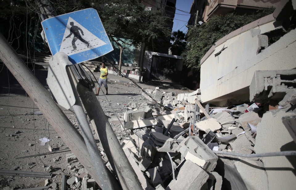 Photo - A Palestinian man walks next to a destroyed house following an overnight Israeli strike in Gaza City Friday, July 25, 2014. Early Friday, Israeli warplanes struck tens of houses throughout the Gaza Strip as international efforts continue to broker a cease fire in the 18 day-old war. (AP Photo/Khalil Hamra)