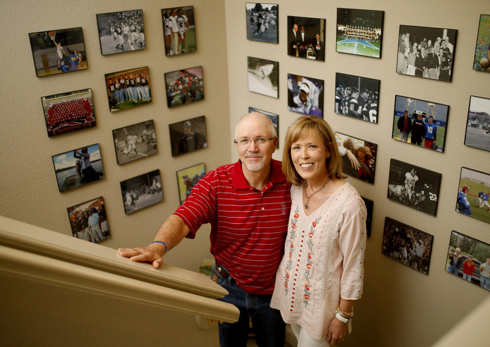Photo - Mike and Marilyn Riley pose for a photo by pictures of their sons, Lincoln Riley, Oklahoma's offensive coordinator, and Garret Riley, inside their home in Muleshoe, Texas, on Thursday, June 25, 2015. Photo by Bryan Terry, The Oklahoman