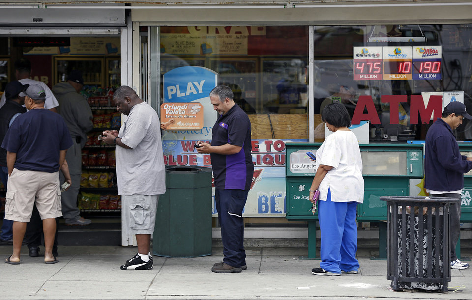Photo - People line up to buy lottery tickets at the Bluebird Liquor store in Hawthorne, Calif. Thursday, May 16, 2013. The multi-state lottery's website said the Powerball drawing jackpot has soared to at least $550 million for next drawing to be held Saturday. (AP Photo/Damian Dovarganes)
