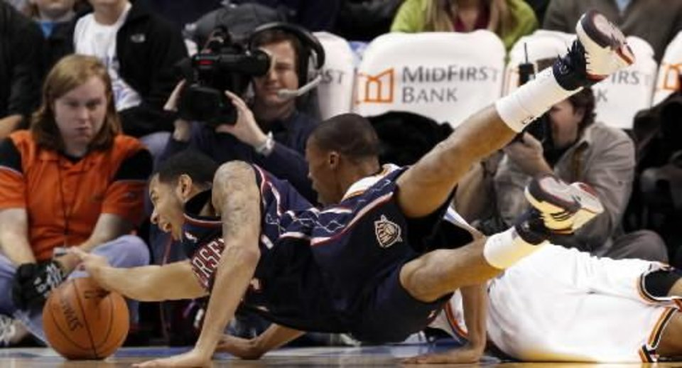 New Jersey's Devin Harris (34) and Oklahoma City's  Russell  Westbrook (0) chase a loose ball in the first half of the NBA basketball game between the Oklahoma City Thunder and the New Jersey Nets at the Ford Center in Oklahoma City, Monday, January 26, 2009. BY NATE BILLINGS