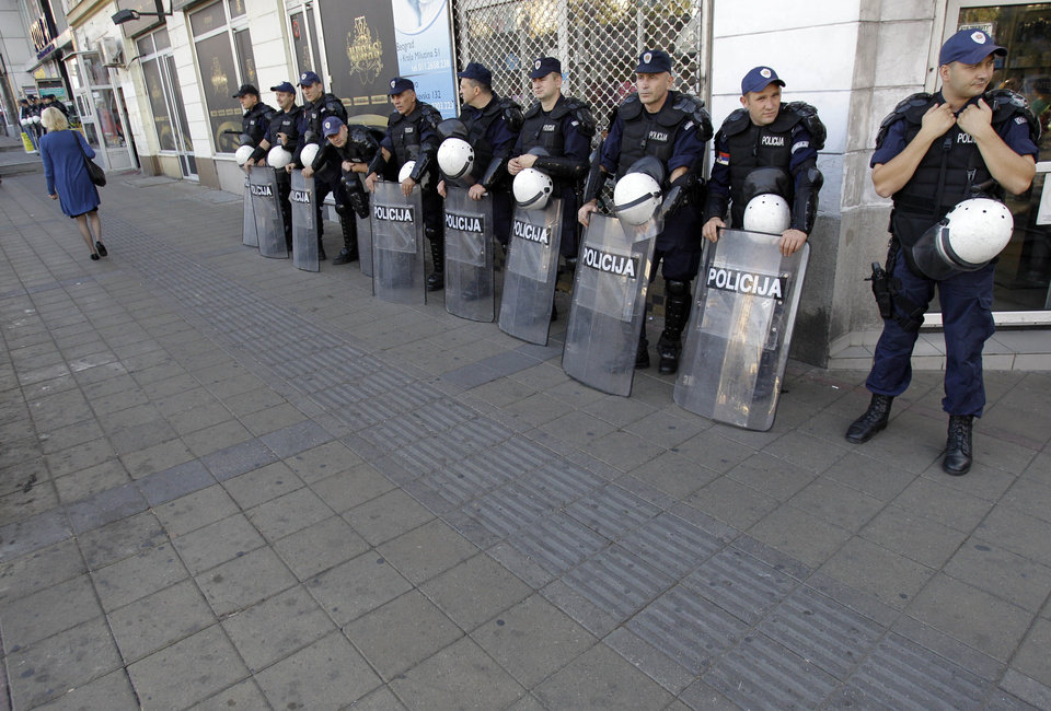 Photo -   A woman passes by Serbian riot policemen cordon near the an art exhibition gallery in Belgrade, Serbia, Wednesday, Oct 3, 2012. Meanwhile, some 2,000 of riot policemen were deployed on Wednesday in front of an art exhibition in Belgrade organized by gay activists which the extremists had threatened to disrupt. Serbia's police on Wednesday banned a gay pride march in Belgrade, citing security concerns but also complying with a request from Serbia's Christian Orthodox church. (AP Photo/Darko Vojinovic)