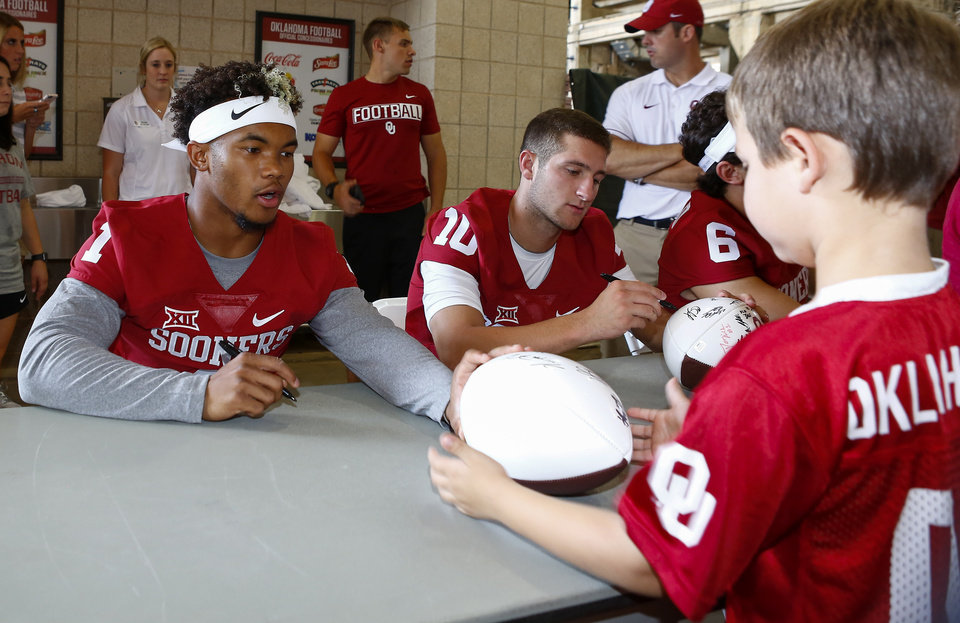 Photo - Oklahoma quarterback Kyler Murray, left, autographs a football for a fan during fan and media day at The Gaylord Family Oklahoma Memorial Stadium in Norman, Okla. on Saturday, Aug. 6, 2016. (Photo by Alonzo J. Adams for the Oklahoman)