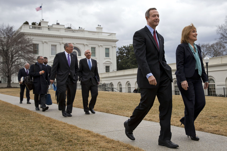 Photo - Maryland Governor Martin O'Malley, front left, and New Hampshire Governor Maggie Hassan, front right, lead fellow Democratic governors as they walk from the White House in Washington, Friday, Feb. 21, 2014, to meet with the media following a meeting with President Barack Obama and Vice President Joe Biden.  (AP Photo/Jacquelyn Martin)