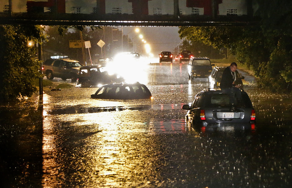 Photo - A man stands on top of his car as it is flooded on S. May Ave near SW 25th in Oklahoma City, Friday, May 31, 2013. Photo by Chris Landsberger, The Oklahoman.