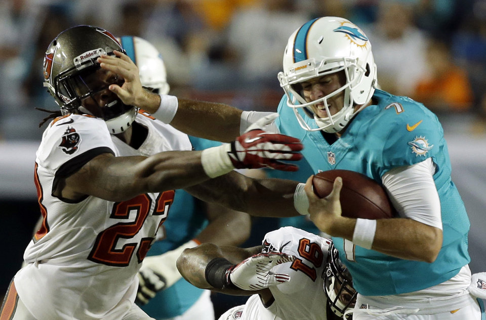 Photo - Miami Dolphins quarterback Pat Devlin (7) stiff-arms Tampa Bay Buccaneers strong safety Mark Barron (23) during the second half of an NFL preseason football game on Saturday, Aug. 24, 2013, in Miami Gardens, Fla. (AP Photo/Lynne Sladky)