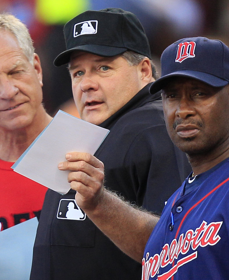 Photo -   Home plate umpire Jerry Layne, center, goes over the ground rules with Minnesota Twins first base coach Jerry White, right, prior to the Twins' baseball game against the Cincinnati Reds, Friday, June 22, 2012 in Cincinnati. Layne left the game and was taken to the hospital to be checked after being hit in the head with the barrel of a broken bat in the fourth inning. Minnesota won 5-4. (AP Photo/Al Behrman)