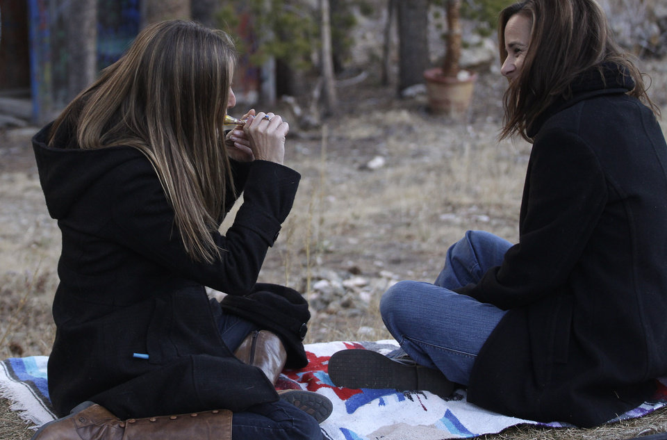 Photo - In this Nov. 19, 2012 photo, two women smoke marijuana together, behind a home in the woods near the small Rocky Mountain town of Nederland, Colo. On Nov. 6, 2012, Colorado and Washington state legalized the recreational use of marijuana. The two states, both culturally and politically, offered fertile ground for legalization advocates - Washington for its liberal politics, Colorado for its libertarian streak, and both for their Western independence. (AP Photo/Brennan Linsley)