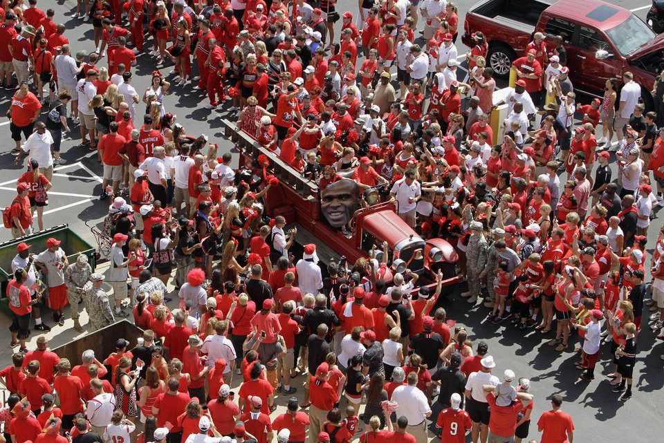Photo - A vintage fire truck opens the walkway for the University of Louisville football team's march into the stadium before the season opening  NCAA college football game against unranked Ohio University in Louisville, Ky., Sunday, Sept. 1, 2013. (AP Photo/Garry Jones)