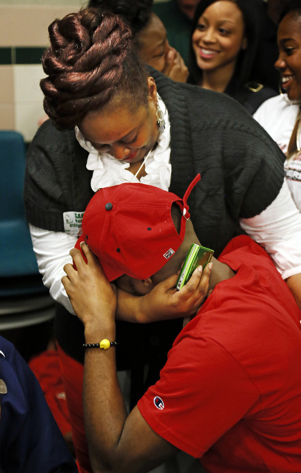 Photo - Eric Davis cries in the arms of his mother, Sheri Davis, after signing to play football at Northwestern Oklahoma State University during the signing day ceremony at Edmond Santa Fe High School in Edmond, Okla., Wednesday, Feb. 6, 2013. Photo by Nate Billings, The Oklahoman
