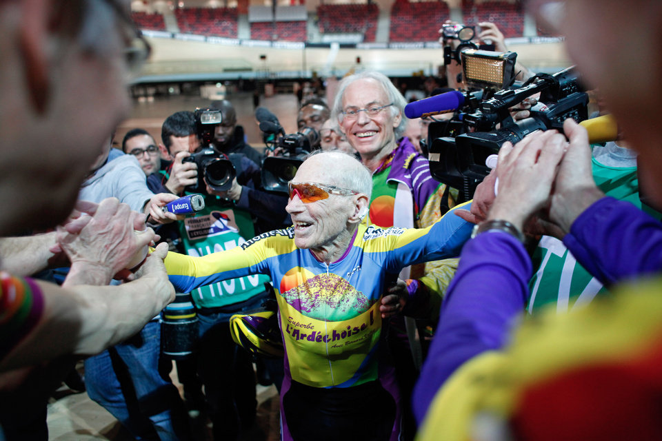 Photo - French cyclist Robert Marchand, aged 102, celebrates with fans after beating his record for distance cycled in one hour, at the velodrome of Saint-Quentin en Yvelines, outside Paris, Friday, Jan. 31, 2014. The 102-year-old broke his own world record in the over-100s category Friday, riding 26.927 kilometers (16.7 miles) in one hour, more than 2.5 kilometers better than his previous best time in the race against the clock two years ago. (AP Photo/Thibault Camus)