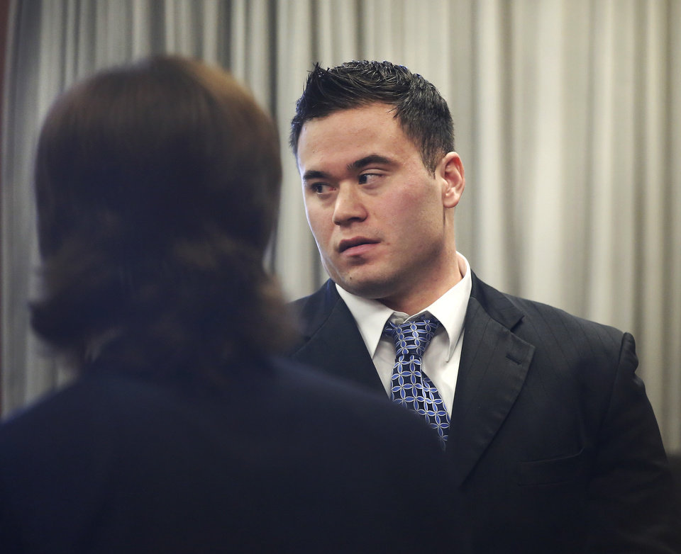 Photo - Daniel Holtzclaw talks to friends in the courtroom during a brief break in his preliminary hearing. Three women testified in an Oklahoma County courtroom   that an Oklahoma City police officer sexually assaulted them while the officer was on duty. The women testified Monday , Nov. 17, 2014, during a preliminary hearing for 27-year-old Daniel Holtzclaw, who is accused of 32 counts of rape, sexual battery and other charges involving 13 women. Holtzclaw has pleaded not guilty.   Photo by Jim Beckel, The Oklahoman