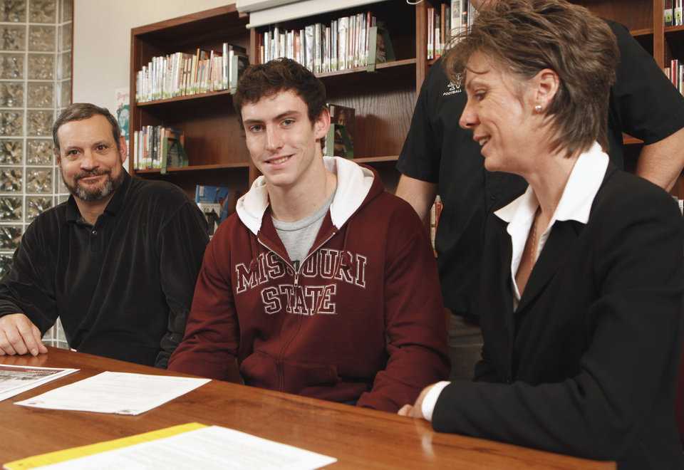Norman North football player Nick Canavan, surrounded by parents Rick and Karen Canavan, signs a letter of intent to play for Missouri State in the high school's library on Wednesday, Feb 3, 2010, in Norman, Okla.  Photo by Steve Sisney, The Oklahoman
