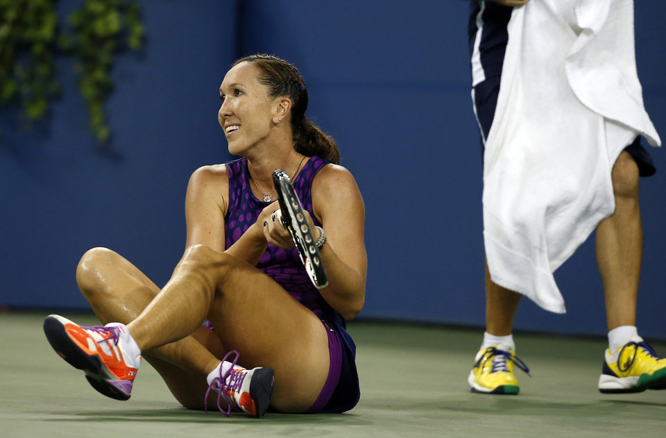 Photo - Jelena Jankovic, of Serbia, sits on the court after slipping during her match against Belinda Bencic, of Switzerland, in the fourth round of the 2014 U.S. Open tennis tournament, Sunday, Aug. 31, 2014, in New York. (AP Photo/Elise Amendola)