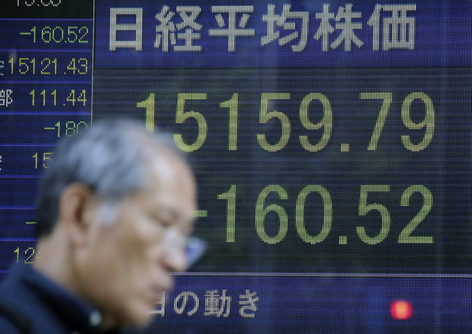 Photo - A man walks by an electronic stock board of a securities firm in Tokyo, Wednesday, Aug. 6, 2014. Worries over Russian troops amassing near the Ukraine border sent most Asian stock markets lower Wednesday. (AP Photo/Eugene Hoshiko)