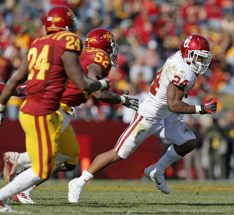 Photo - Oklahoma's Brennan Clay (24) carries the ball away from Iowa State's Jeremiah George (52) and Durrell Givens (24) in the third quarter during a college football game between the University of Oklahoma (OU) and Iowa State University (ISU) at Jack Trice Stadium in Ames, Iowa, Saturday, Nov. 3, 2012. OU won, 35-20. Photo by Nate Billings, The Oklahoman
