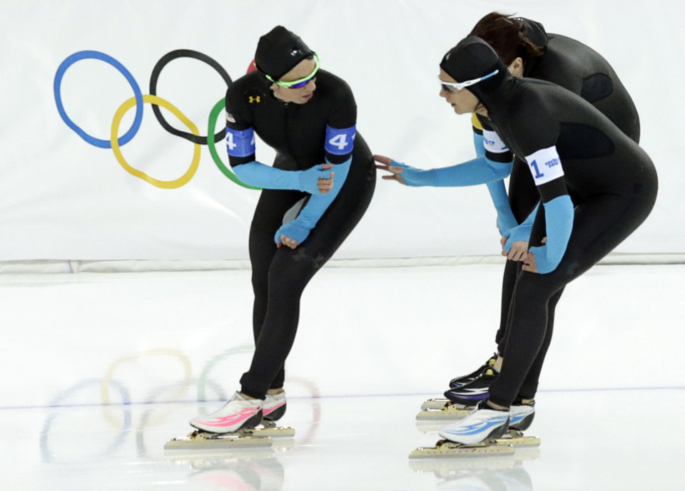 Photo - U.S. speedskaters Jilleanne Rookard, left, Brittany Bowe, front right, and Heather Richardson catch their breath after the women's speedskating team pursuit quarterfinals at the Adler Arena Skating Center at the 2014 Winter Olympics, Friday, Feb. 21, 2014, in Sochi, Russia. (AP Photo/Matt Dunham)