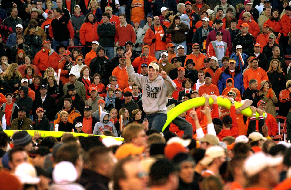 An OSU fan rides on a goal post as Cowboys fans celebrate OSU's win over in-state rival OU, 38-28, after the Bedlam college football game on Nov. 30, 2002 in Stillwater, Okla. Staff photo by Jim Beckel.