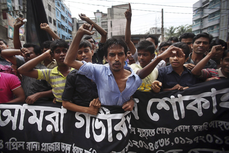Photo - Workers at a garment factory just streets away from the recently collapsed garment factory building, protest as they refuse to work when they found cracks in their current office building, Tuesday, April 30, 2013 in Savar, near Dhaka, Bangladesh.   A top Bangladesh court on Tuesday ordered the government to