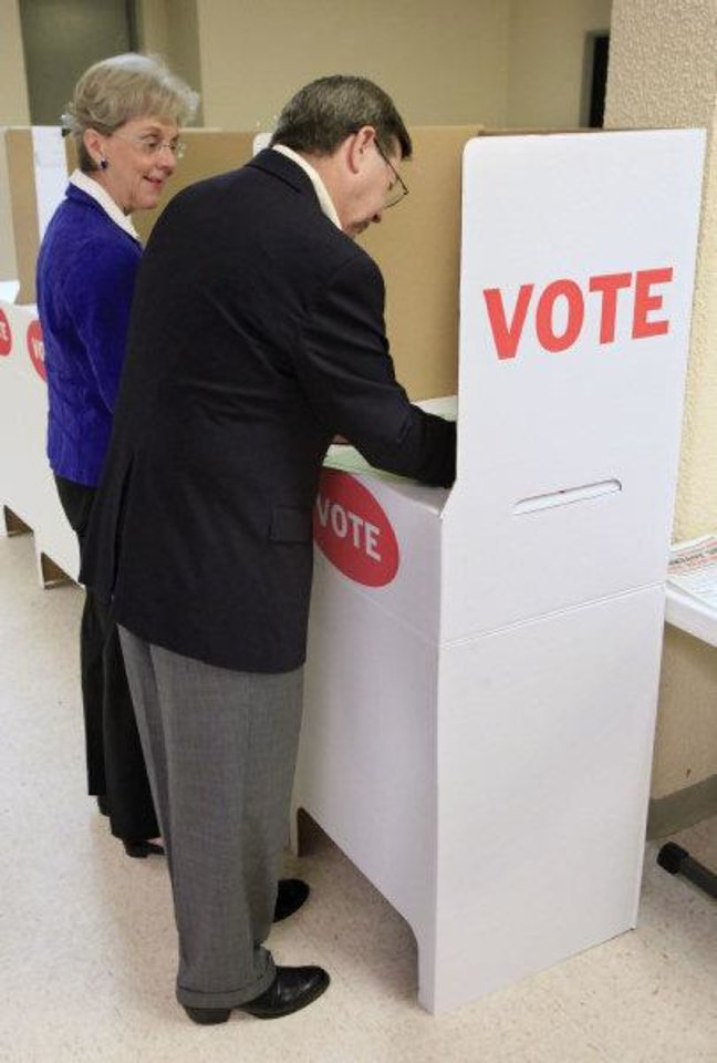 Attorney General Drew Edmondson, gubernatorial candidate, marks his ballot as his wife Linda Edmondson looks at his choices in the voting booths at precinct 574, Sooner and Hefner roads in northeast Oklahoma City Tuesday  <strong>PAUL B. SOUTHERLAND - PAUL B. SOUTHERLAND</strong>