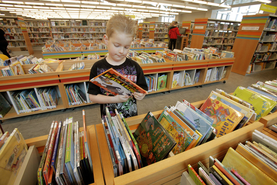Cooper Dennehy, 6, of Oklahoma City, looks at a book Wednesday in the children�s area at the Southwest  Oklahoma City Public Library. Photo by Paul B. Southerland, The Oklahoman