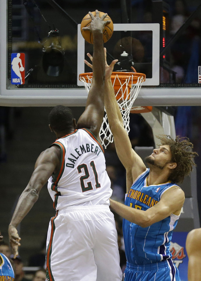 Milwaukee Bucks' Samuel Dalembert(21) dunks the ball over New Orleans Hornets' Robin Lopez during the first half of an NBA basketball game Saturday, Nov. 17, 2012, in Milwaukee. (AP Photo/Jeffrey Phelps)