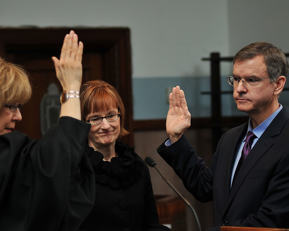 Oklahoma County Court Clerk Tim Rhodes is sworn in Wednesday by state Supreme Court Judge Noma Gurich, as his wife, Sherry, watches.