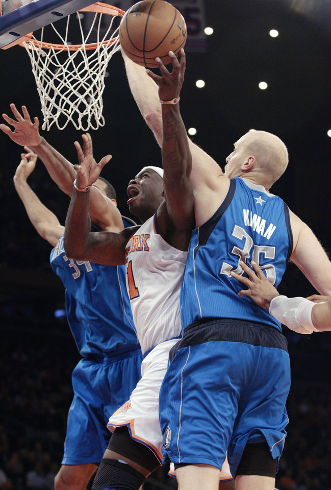 New York Knicks' Ronnie Brewer (11) splits Dallas Mavericks' Brandan Wright (34) and Chris Kaman (35) during the first half of an NBA basketball game Friday, Nov. 9, 2012, in New York. (AP Photo/Frank Franklin II)