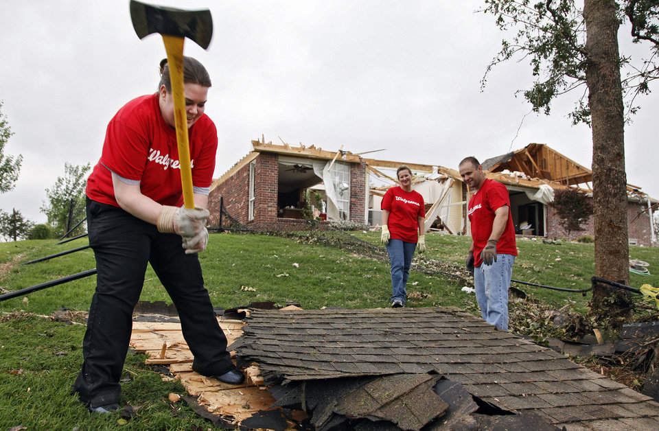 Walgreens volunteer Cassidy Climer swings an axe to break up a piece of roofing as she helps clean up debris and damage on Wednesday, May 12, 2010, in Oklahoma City, Okla. left behind by the tornados that hit central oklahoma on Monday. Photo by Chris Landsberger, The Oklahoman