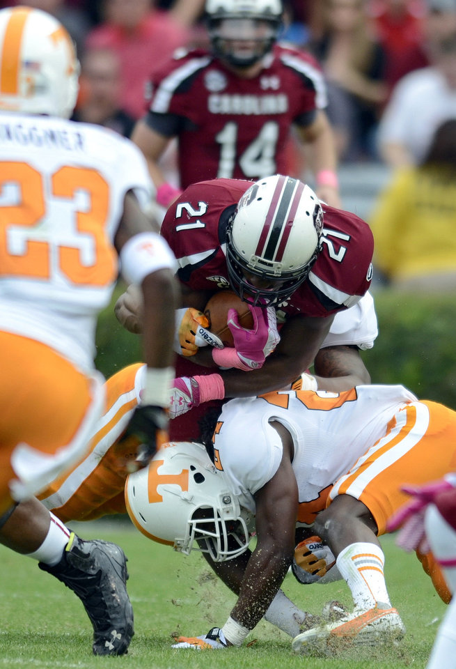 Photo -   South Carolina running back Marcus Lattimore (21) is hit by Tennessee's Eric Gordon during the first half of an NCAA college football game Saturday, Oct. 27, 2012 at Williams-Brice Stadium in Columbia, S.C. Lattimore was injured on the play. (AP Photo/Richard Shiro)