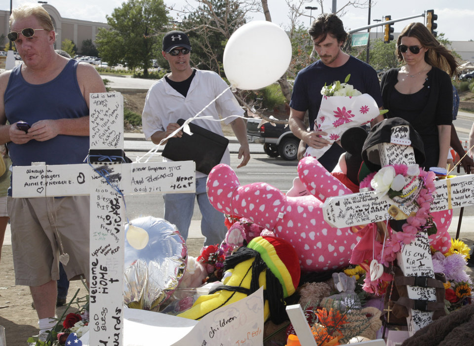 Photo -   Actor Christian Bale and his wife Sibi Blazic, at right, carry flowers to place on a memorial to the victims of Friday's mass shooting, Tuesday, July 24, 2012, in Aurora, Colo. Twelve people were killed when a gunman opened fire during a late-night showing of the movie