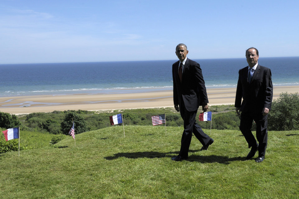 Photo - US President Barack Obama, left, and  French President Francois Hollande look out over Omaha beach during a joint French-US D-Day commemoration ceremony at the Normandy American Cemetery and Memorial in Colleville-sur-mer, Normandy, France, Friday June 6, 2014, marking the 70th anniversary of the World War II Allied landings in Normandy. (AP Photo/Alain Jocard, pool)