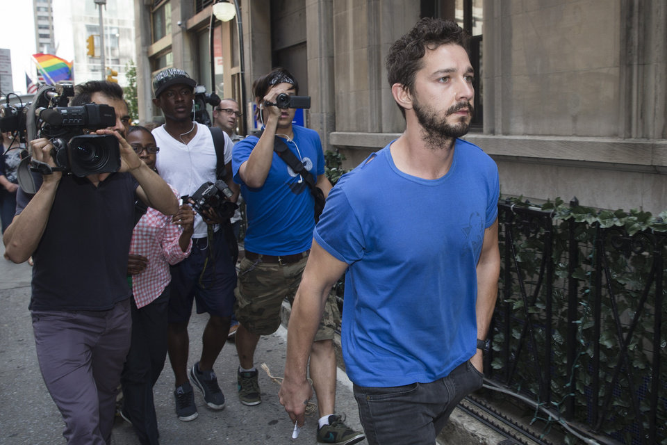 Photo - Actor Shia LaBeouf walks through the media after leaving Midtown Community Court following his arrest the previous day for yelling obscenities at a Broadway performance of