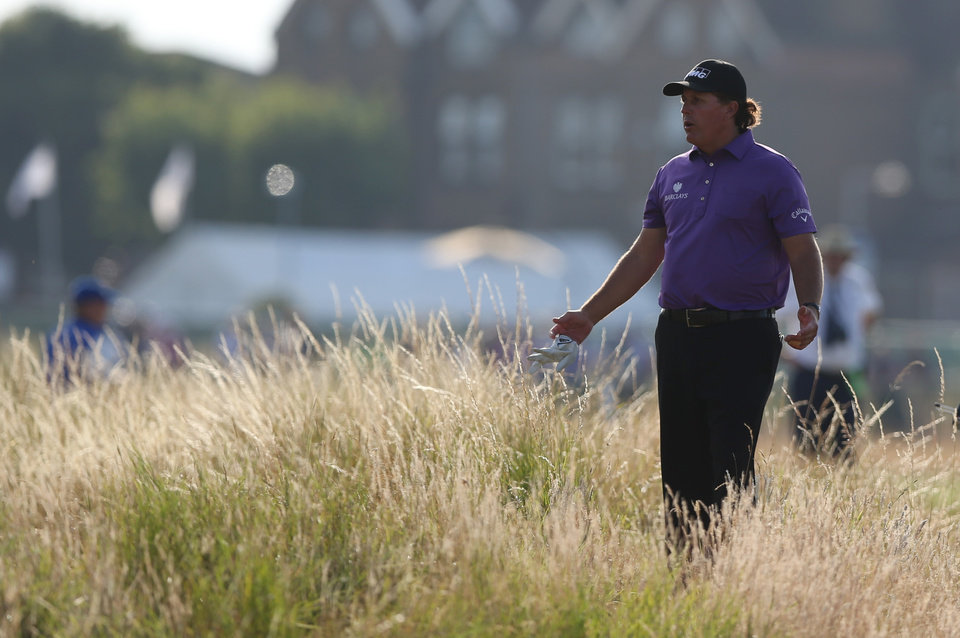 Photo - Phil Mickelson of the US looks for his ball in the rough on the 18th hole during the first day of the British Open Golf championship at the Royal Liverpool golf club, Hoylake, England, Thursday July 17, 2014. (AP Photo/Jon Super)