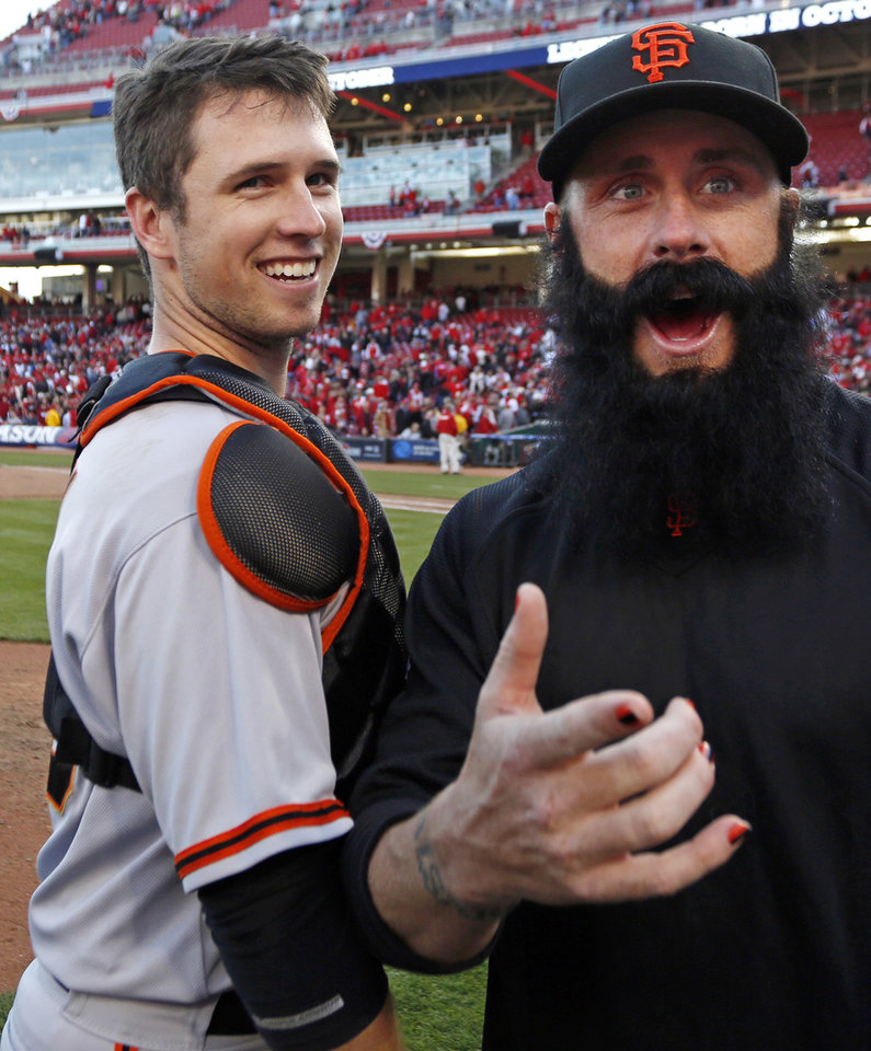 Photo -   San Francisco Giants' Buster Posey celebrates with pitcher Brian Wilson after they defeated the Cincinnati Reds 6-4 in Game 5 of the National League division baseball series, Thursday, Oct. 11, 2012, in Cincinnati. The Giants won the final three games, all in Cincinnati, and advanced to the NL championship series. (AP Photo/David Kohl)