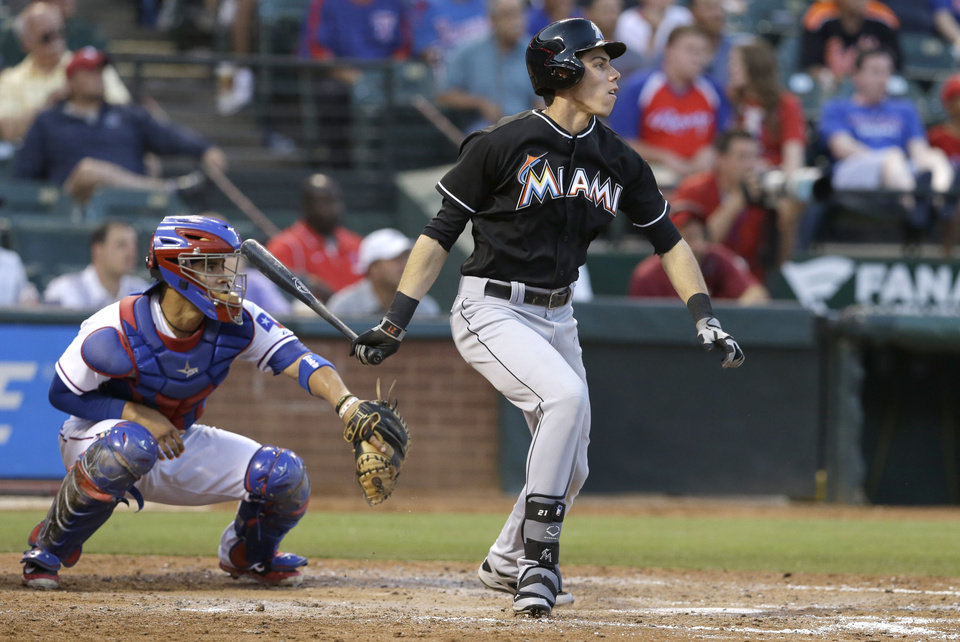 Photo - Miami Marlins Christian Yelich, right, watches his two run double to center field with Texas Rangers catcher Robinson Chirinos (61) looking on during the fourth inning of a baseball game in Arlington, Texas, Tuesday, June 10, 2014. Marlins Justin Bour and Jeff Mathis scored. (AP Photo/LM Otero)