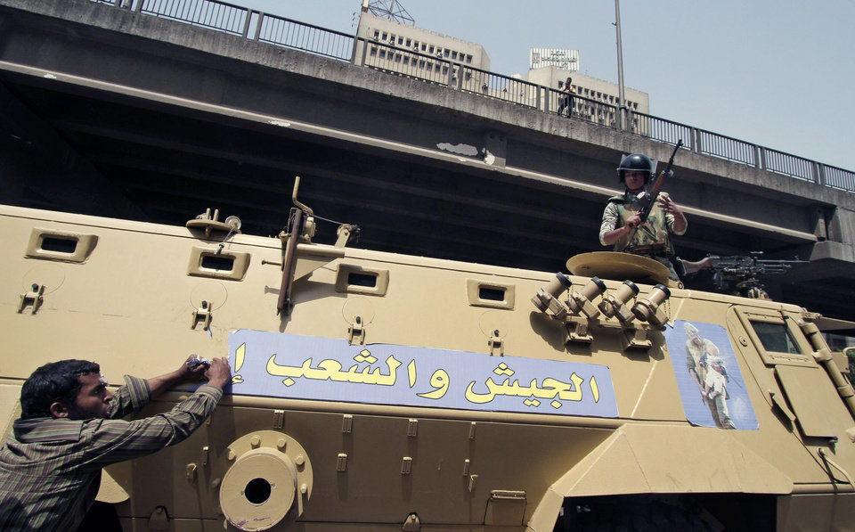 Photo -   An Egyptian protester rips a banner on a military tank with Arabic writing that reads: