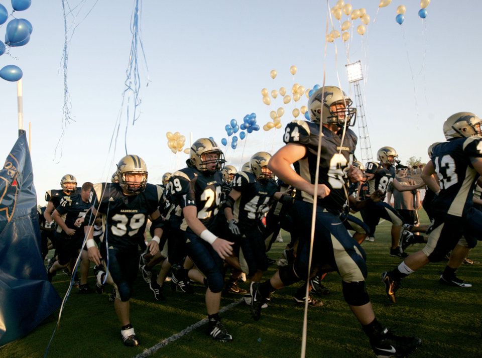 Photo - ENTER, ENTRANCE: The Southmoore Sabercats take the field before their first high school football game against Edmond Memorial in Moore, Okla., Thursday, September 4, 2008.  BY BRYAN TERRY, THE OKLAHOMAN ORG XMIT: KOD